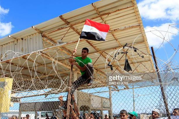 A Palestinian protestor puts up an Egyptian flag on barbed wire during a rally in front of the Rafah border crossing in the southern Gaza Strip on...