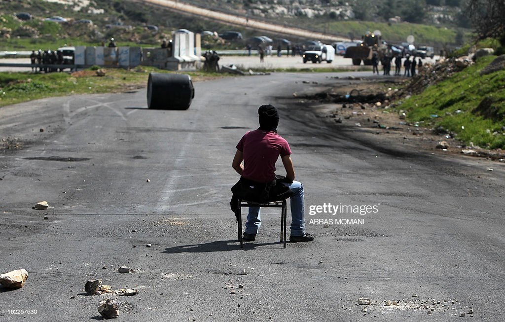 A Palestinian protestor sits facing Israeli soldiers during clashes next to Ofer prison, near the West Bank city of Ramallah, following a demonstration in support of Palestinian detainee, Samer Issawi, who has been on hunger strike for more than 200 days, and other prisoners on hunger strike in Israeli prisons on February 21, 2013. Israel's Supreme Court rejected an appeal by a hunger-striking Palestinian prisoner on February 20, saying it was not authorised to overrule the restrictive military order under which he had been jailed.
