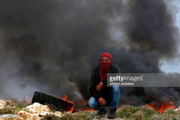 Palestinian protestor squats in front of smoke during clashes with Israeli security forces following a demonstration against Jewish settlements in...