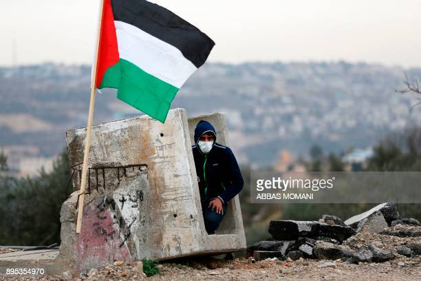 A Palestinian protestor takes cover in a concrete block flying the Palestinian flag during clashes with Israeli security forces at Atarot checkpoint...