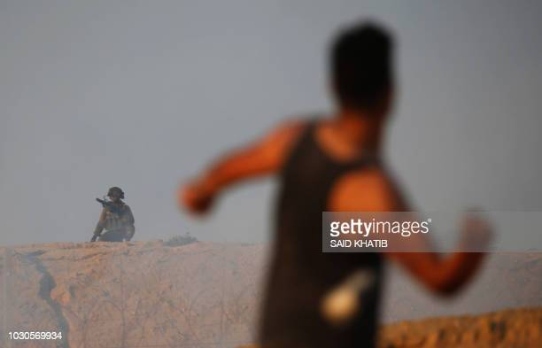 A Palestinian protestor throws a stone towards Israeli forces on the beach near the maritime border with Israel in the northern Gaza Strip during a...