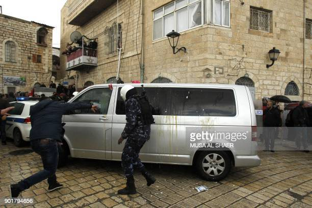 A Palestinian protestor throws eggs at the convoy of Jerusalem's Greek Orthodox patriarch Theophilos III in the West Bank town of Bethlehem on...