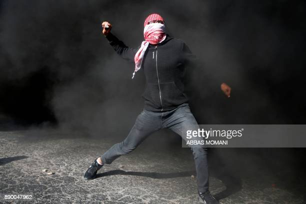 Palestinian protestor throws stones towards Israeli security forces during clashes in the West Bank city of Ramallah on December 11 2017 as protests...