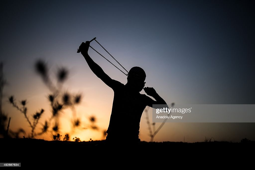 A Palestinian protestor uses a sling shot to throw stones at Israeli soldiers near the border fence between Israel and the Gaza Strip after clashes occurred during a protest against Israeli violations near Bureij in the central Gaza Strip on October 14, 2015.