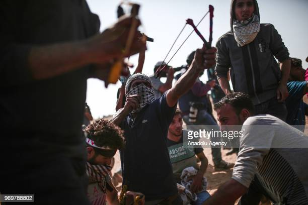 Palestinian protestor uses a slingshot to throw rock towars Israeli security forces during March of the Million for Jerusalem protests marking the...
