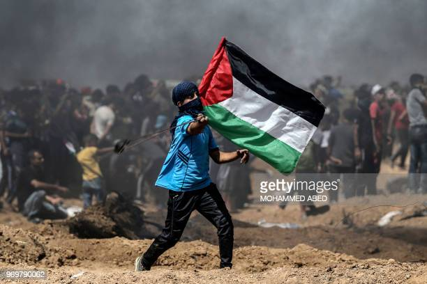 A Palestinian protestor waves his national flag during a demonstration along the border with Israel east of Jabalia in the central Gaza Strip on June...