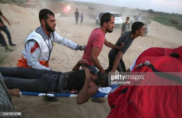 TOPSHOT Palestinian protestors and paramedics carry a wounded man during a demonstration on the beach near the maritime border with Israel in the...