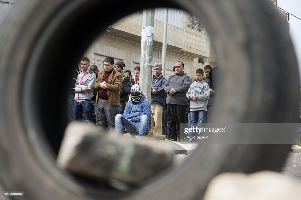 Palestinian protestors are seen through a car tire as they perform Friday prayers next to Ofer prison, near the West Bank city of Ramallah, following a demonstration in support of Palestinian detainees on hunger strike in Israeli prisons on February 22, 2013. Palestinians demanding the release of hunger-striking prisoners clashed with Israelis in the West Bank and east Jerusalem, as three fasting inmates were taken to hospitals.