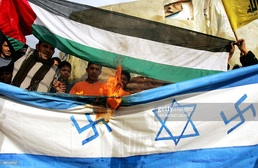 Palestinian protestors burn a makeshift Israeli flag, bearing Nazi swastikas on each side of the Star of David, during a demonstration against Israel's continuing assault on Gaza in the refugee camp of Ain el-Hilweh near the southern Lebanese port city of Sidon on December 30, 2008. Arab capitals have been the scene for daily protests since December 27 against the continuing Israeli onslaught in the Gaza Strip that has killed more than 360 Palesitnians. Israel today readied troops on the Gaza border and warned its assault on Hamas could last for weeks, as jets pummelled Islamist targets for a fourth day amid a diplomatic push for a truce.