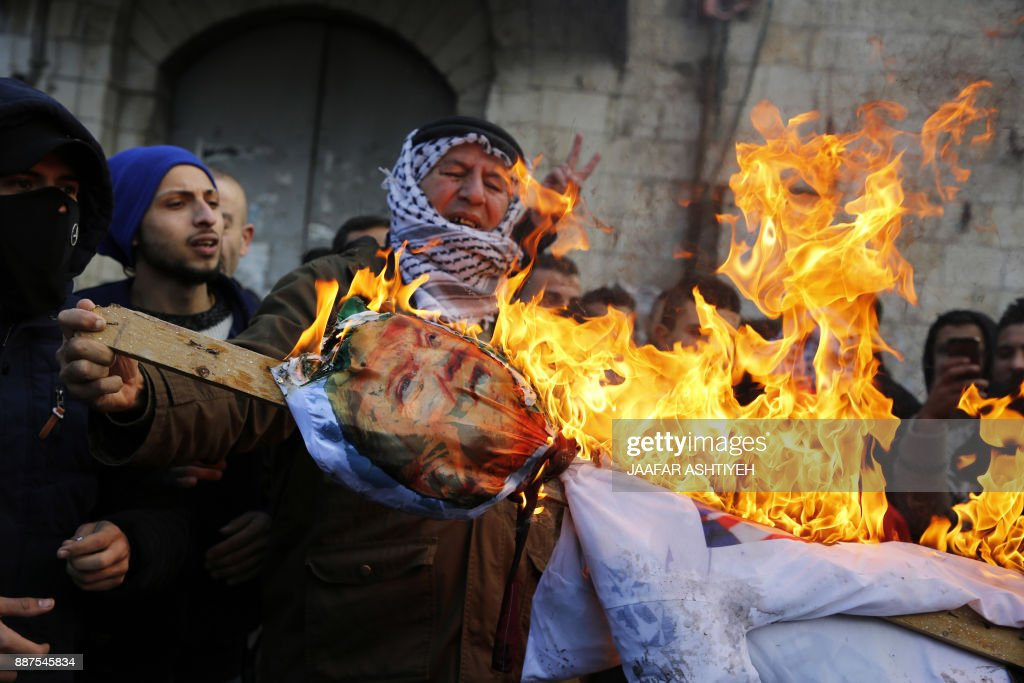 TOPSHOT - Palestinian protestors burn an effigy of US President Donald Trump following his decision to recognise Jerusalem as the capital of Israel, in the West Bank city of Nablus, on December 7, 2017. / AFP PHOTO / Jaafar ASHTIYEH