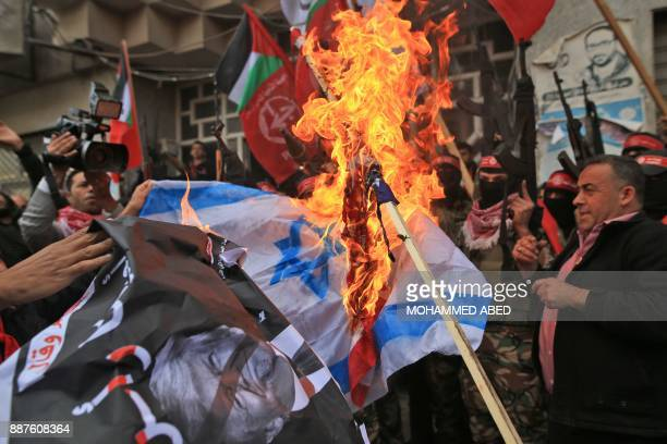 Palestinian protestors burn the Israeli flag and a poster of US President Donald Trump following his decision to recognise Jerusalem as the capital...