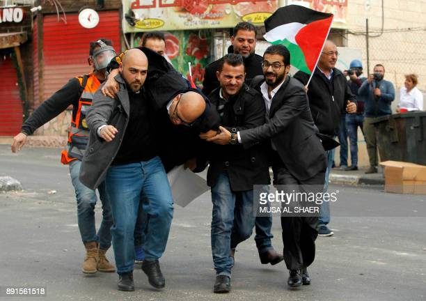 TOPSHOT Palestinian protestors carry a man wounded by a rubber bullet during clashes following a demonstration in the occupied West Bank city of...