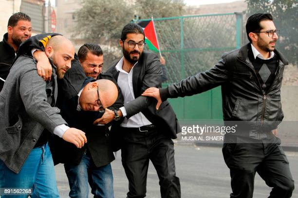 Palestinian protestors carry a man wounded by a rubber bullet during clashes following a demonstration in the occupied West Bank city of Bethlehem on...