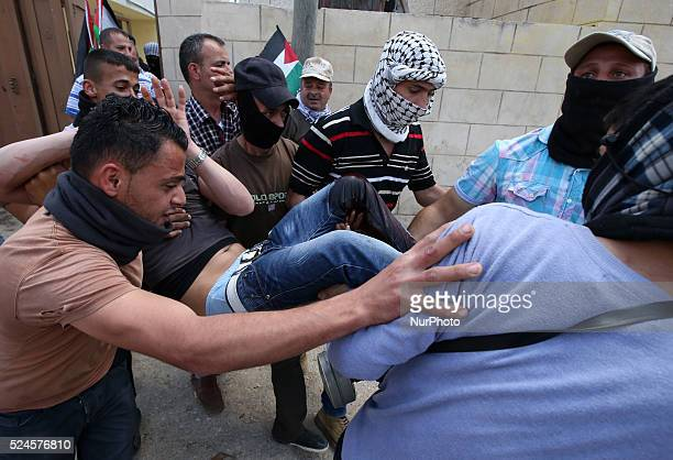 Palestinian protestors carry a wounded comrade who was reportedly shot in the foot by a member of the Israeli soldiers during clashes with Israeli...