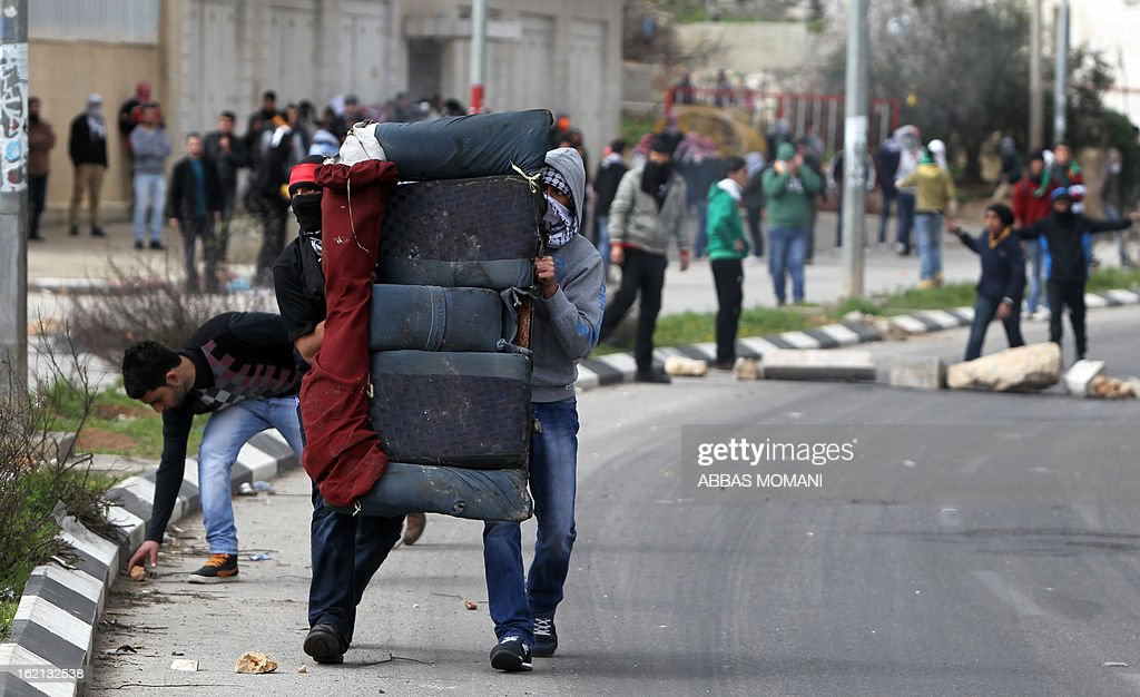 Palestinian protestors carry the back seat of a car to fend off rubber bullets from Israeli soldiers during a protest in support of prisoners on hunger strike in Israeli prisons, near Ramallah on February 19, 2013. Some 800 Palestinians serving time in Israeli jails were refusing food in solidarity with four fellow inmates who have been on long-term hunger strike, officials said.