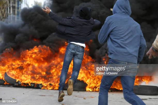 Palestinian protestors clash with Israeli forces near an Israeli checkpoint in the West Bank city of Ramallah on December 7 2017 US President Donald...