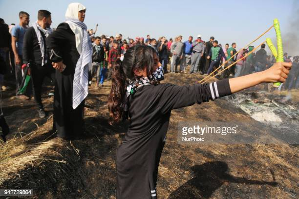 Palestinian protestors gesture during clashes with Israeli security forces on the GazaIsrael border following a protest calling for the right to...