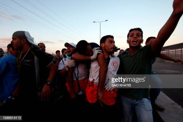 TOPSHOT Palestinian protestors help evacuate a wounded comrade during a demonstration at the Erez crossing with Israel on September 18 in the...