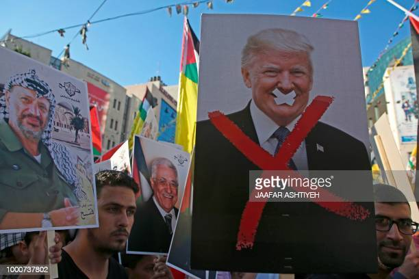 Palestinian protestors hold portraits of late Palestinian leader Yasser Arafat and US President Donald Trump during a rally in support to the Fatah...