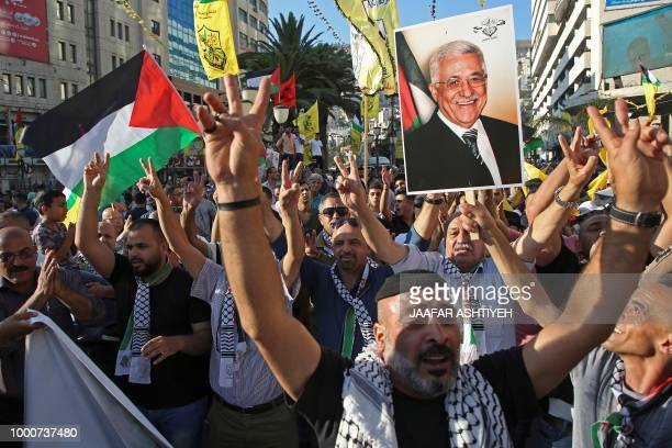 Palestinian protestors hold portraits of Palestinian president Mahmud Abbas during a rally in support to the Fatah movement in the West Bank city of...