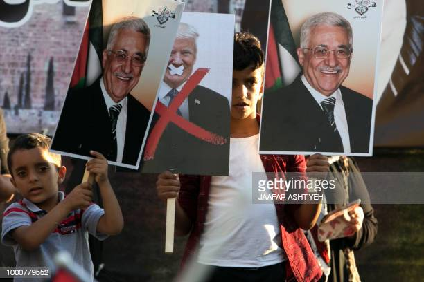 Palestinian protestors hold portraits of Palestinian president Mahmud Abbas and US President Donald Trump during a rally in support to the Fatah...