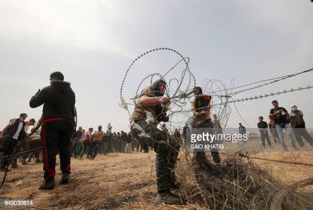 TOPSHOT Palestinian protestors pull barbed wire from the border fence with Israel in Rafah in southern Gaza Strip on April 20 2018 A Palestinian was...