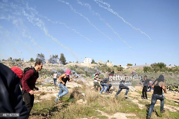 Palestinian protestors run as Israeli security forces fire tear gas during a protest against Israel's violations in Ramallah West Bank on November 14...