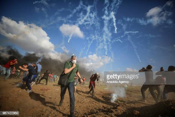 Palestinian protestors run away after Israeli forces fire tear gas along the border between the Gaza Strip and Israel on the 14th week of right of...