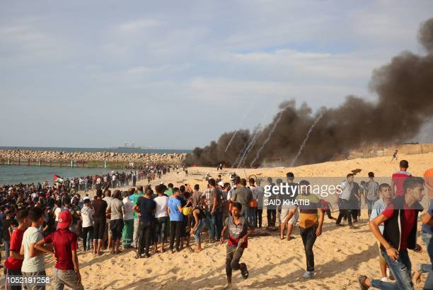 TOPSHOT Palestinian protestors run away from tear gas fired by Israeli security forces during a demonstration on the beach near the maritime border...