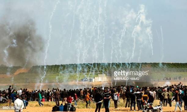 Palestinian protestors run for cover from tear gas fired by Israeli security forces during clashes following a demonstration commemorating Land Day...