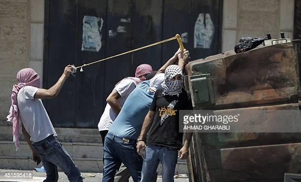 Palestinian protestors throw stones toward Israeli police during clashes in the Shuafat neighborhood in Israeli-annexed Arab East Jerusalem, on July...