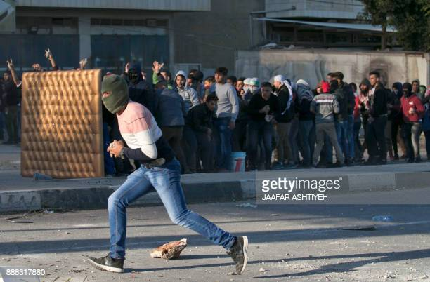 Palestinian protestors throw stones towards Israeli security forces at Hawara checkpoint south of the West Bank city of Nablus during clashes...