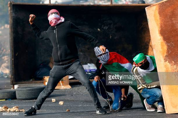 TOPSHOT Palestinian protestors throw stones towards Israeli security forces during clashes in the West Bank city of Ramallah on December 11 2017 as...