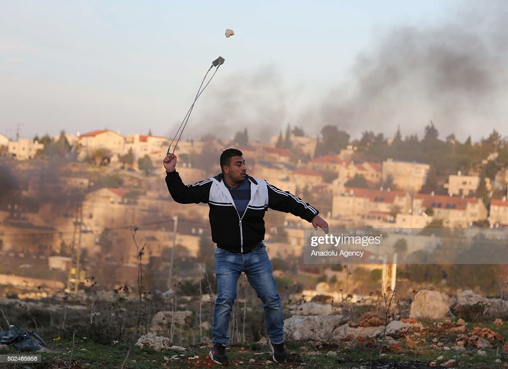 Palestinian protestors throw stones towards Israeli security guards after clashes occurred during a protest against Israeli separation wall around Jalazone refugee camp in Ramallah, West Bank on December 25, 2015.