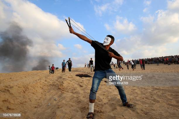 Palestinian protestors use slingshots a demonstration on the beach near the maritime border with Israel, in the northern Gaza Strip, on October 8,...