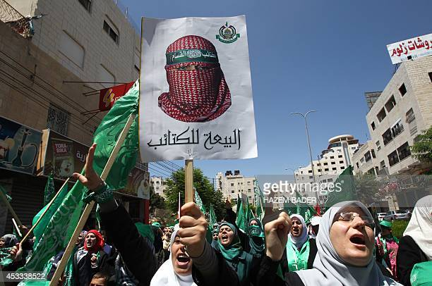 Palestinian protestors wave Islamist flags and hold a poster bearing an image of the Abu Obeida the official spokesperson of the Palestinian militant...