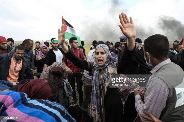 TOPSHOT Palestinian protestors wave their national flag and gesture during a demonstration commemorating Land Day near the border with Israel east of...