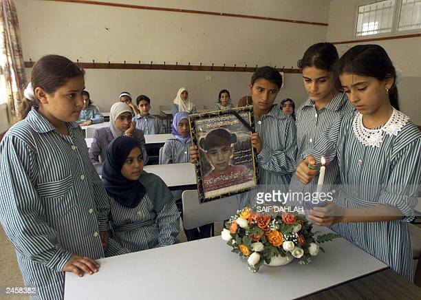 Palestinian pupils light a candle and place a bouquet of flowers at the desk of fellow pupil Riham Ward slain two years ago by an Israeli tank shell...