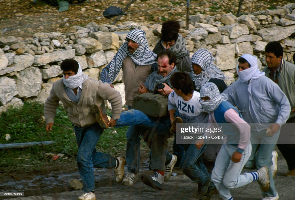 Palestinian rebels carry a wounded photographer away from danger during a protest in the streets of Beit Omar. Violence broke out after rebel Israeli and Palestinian fighters protested in the disputed territory of West Bank during the first Intifada. | Location: Beit Omar, West Bank.