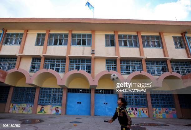 A Palestinian refugee boy plays football infront of a school run by the UN agency for Palestinian refugees UNRWA on January 18 2018 at the alBaqa'a...