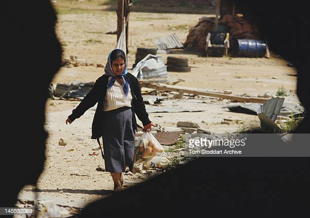Palestinian refugee carrying a bag of vegetables at the Bourj el-Barajneh camp in Beirut, Lebanon, during the Lebanese Civil War, 1989.
