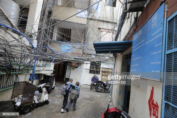 Palestinian refugee children walk past an UNRWA financed medical clinic at the Burj alBarajneh camp in the Lebanese capital Beirut on January 17 2018...