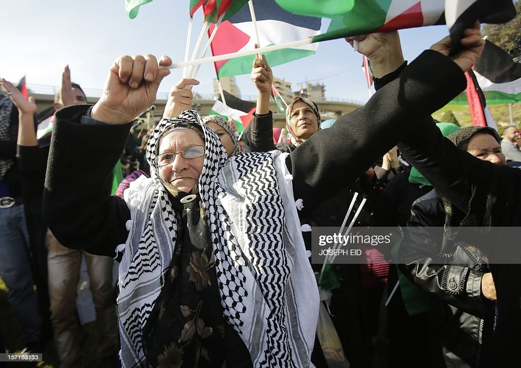 A Palestinian refugee in Lebanon waves her national flag during a gathering outside the United Nations headquarters in Beirut on November 29, 2012 in support of Palestinian leader Mahmud Abbas which is heading to the General Assembly today with huge backing for his bid for UN recognition of statehood despite strong US and Israeli opposition. Abbas will make the case for Palestine to become a UN 'non-member observer state' and indicate his conditions for talks with Israel in a key speech to the 193-member assembly.