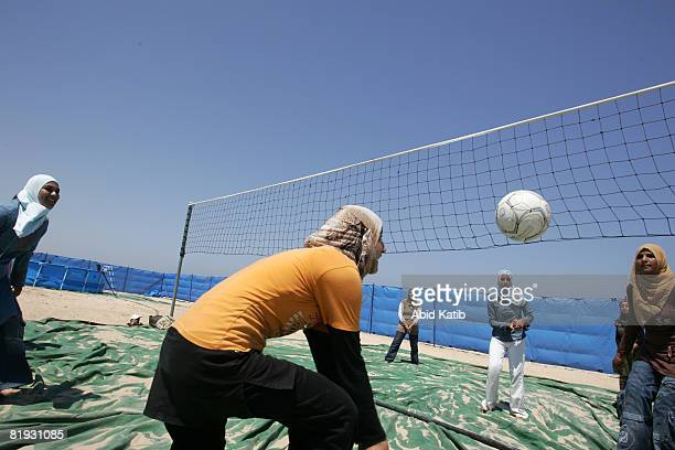 Palestinian refugee school girls play volleyball on the beach as they attend a summer games camp on July 14 2008 in Gaza City Gaza Strip The United...