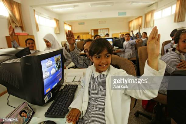 Palestinian refugee schoolgirls raise their hands in The AlShati primary school a United Nations Relief and Works Agency school as they participate...