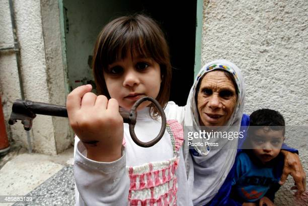 Palestinian refugee, Subhia Abdul Rahim Abu Ghali, 79 years old, with her granddaughter, from the Rafah refugee camp, who holds up a key allegedly...