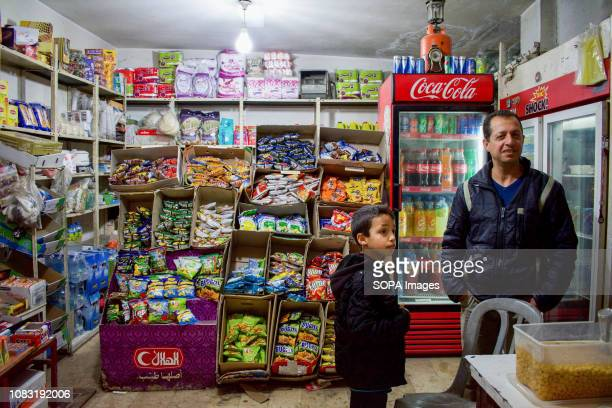 Palestinian refugees are seen in a shop at the Dheisheh refugee camp