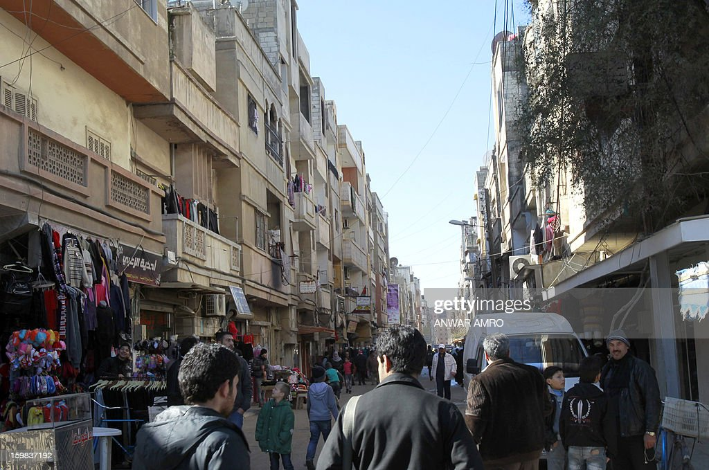 Palestinian refugees are seen walking along a street in the 'Palestine' Palestinian refugee camp in the Syrian city of Homs, on January 21, 2013. Some Palestinian refugee families have fled their homes in the Yarmuk refugee camp in southern Damascus following near by battles between pro-Syrian government troops and rebels forces, moving to the refugee camp in Homs.