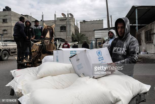 Palestinian refugees collect aid parcels at a United Nations food distribution centre in Khan Yunis in the southern Gaza Strip on January 28 2018 On...