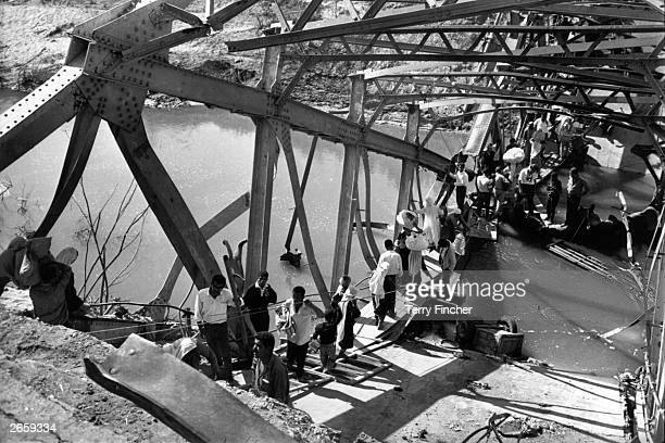 Palestinian refugees crossing the remains of the Allenby Bridge over the River Jordan blown up to prevent Israeli pursuit during the SixDay War